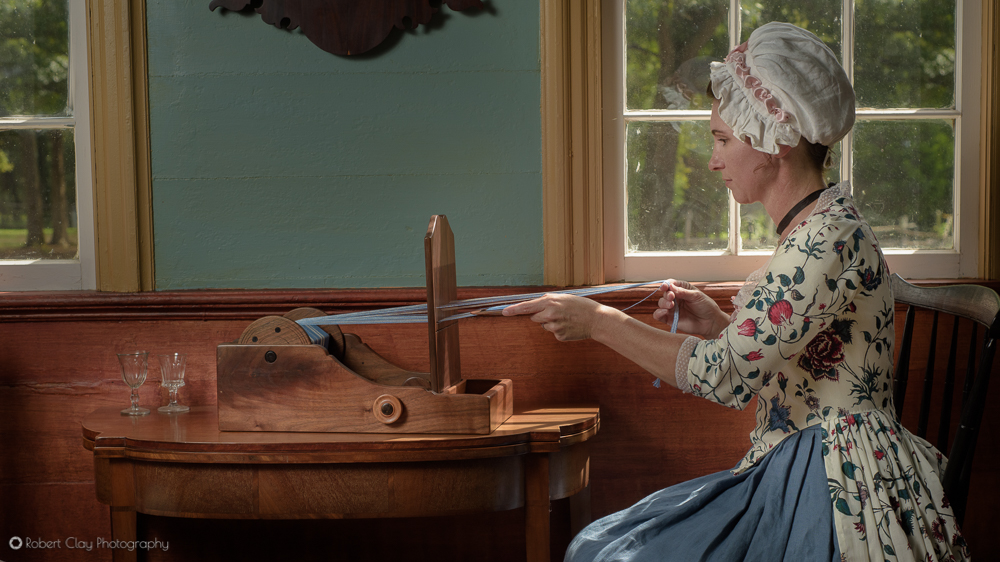 Historic reenactor works with a table top loom in an 18th century setting.